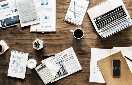 Tafel met laptop, kranten, kop koffie en notities
